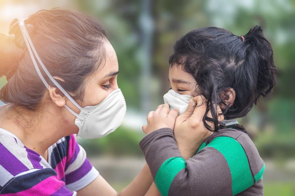 une enfant et sa mère sont de profil et portent un masque ffp2. la mère est en train d'ajuster le masque sur le visage de sa fille.