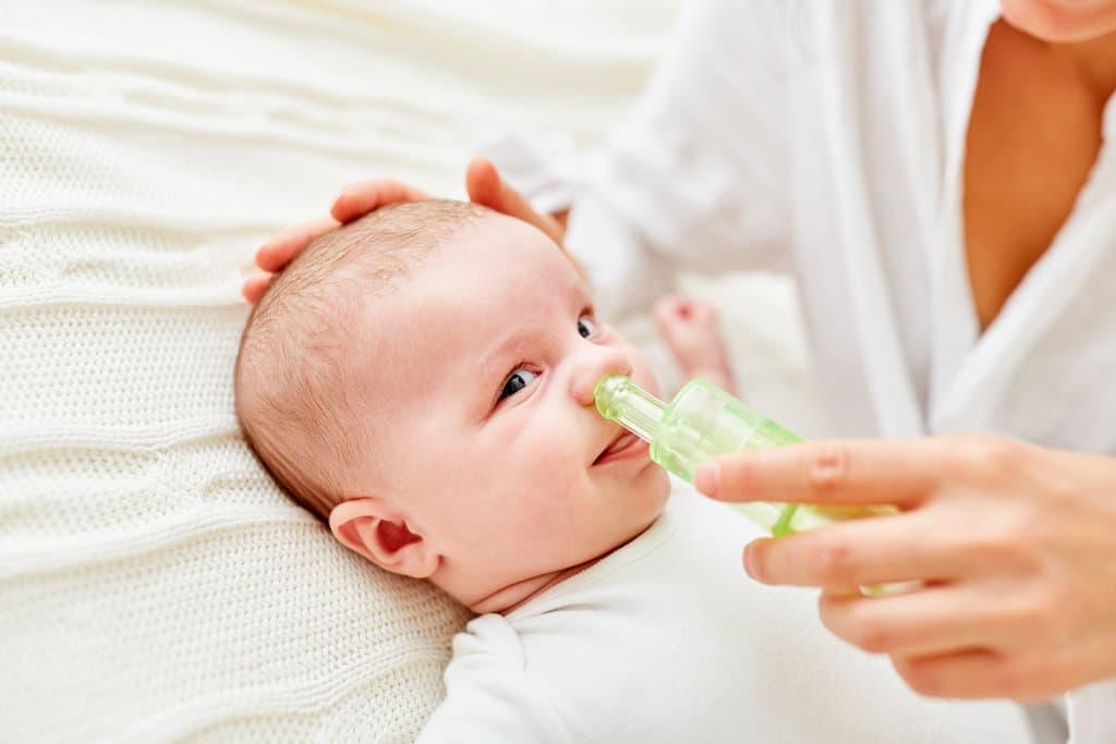 un bébé se fait moucher le nez avec un aspirateur nasale
