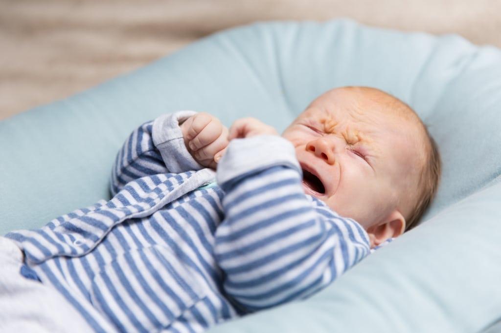 bébé en marinière qui pleure dans son couffin bleu