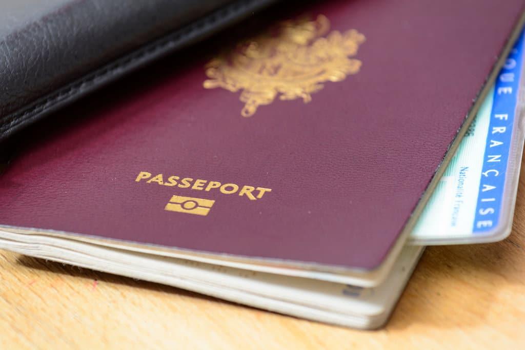gros plan sur un passeport français dans lequel dépasse un bout de carte d'identité française