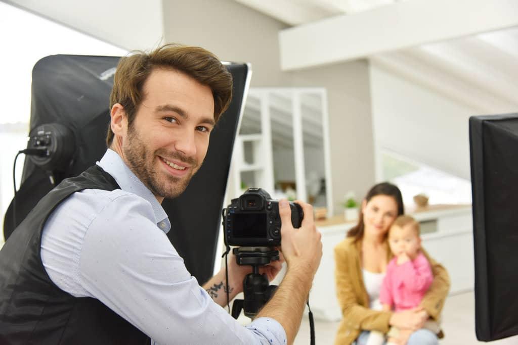 en premier plan un photographe dans un studio sourit à la photo, pendant qu'il a la main sur son appareil photo posé sur un trépied. En arrière plan une femme et un bébé prennent la pose assis.
