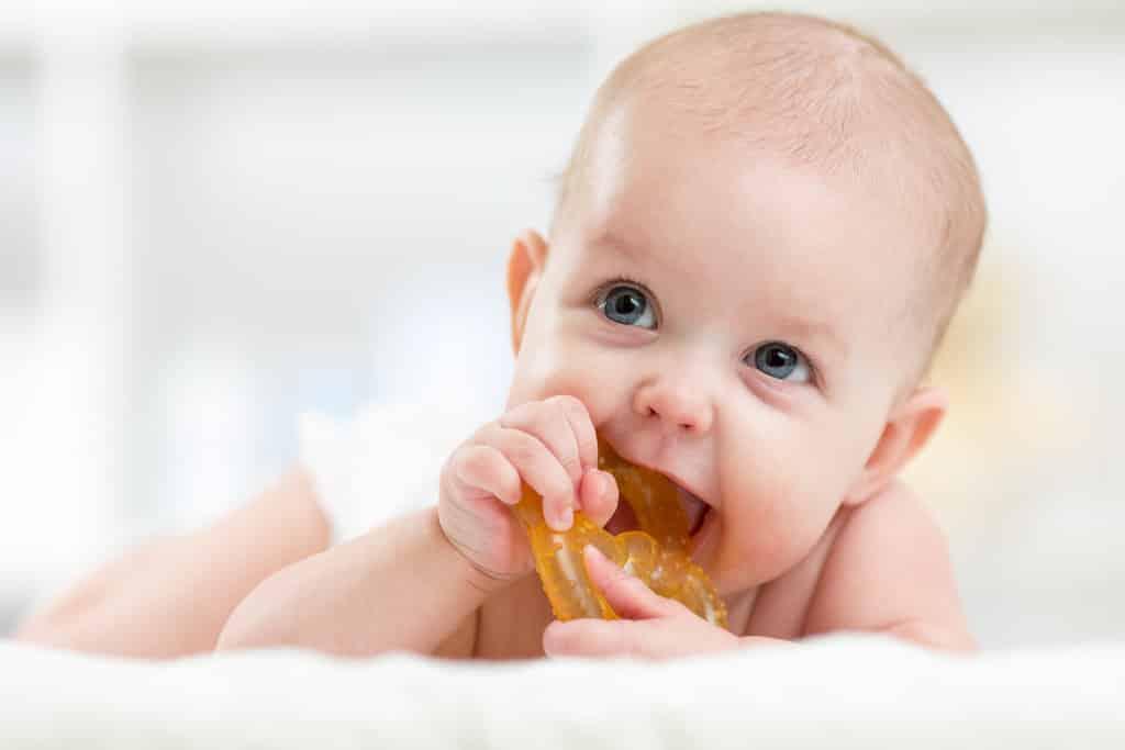 un bébé allongé sur le ventre machouille un anneau de dentition en plastique pour se faire les dents