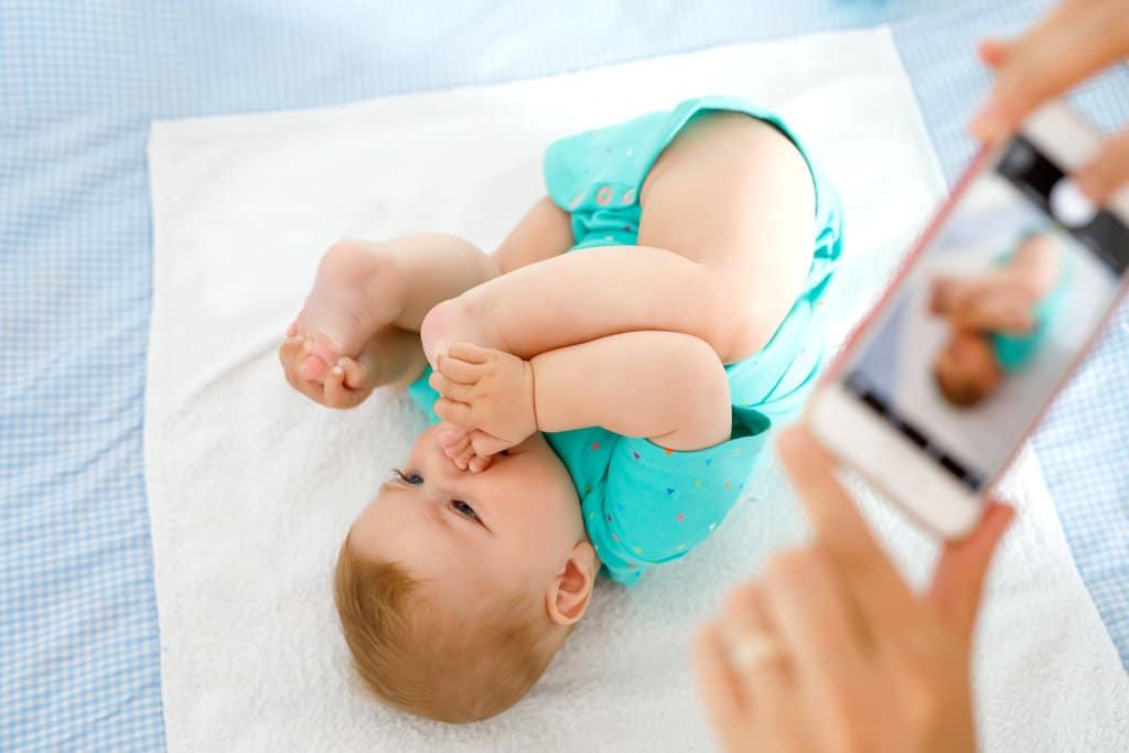 un bébé prend la pose sur une serviette et attrape ses pieds pour les mettre dans sa bouche. en premier plan flouté, on devine les mains d'une personne qui tient un smartphone qui prend le bébé en photo.