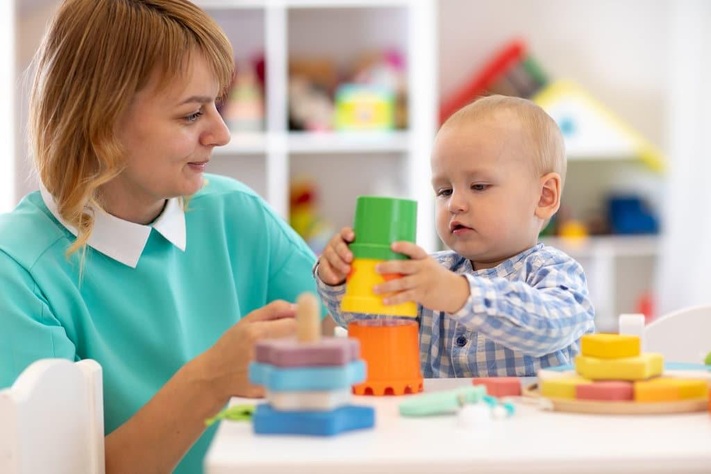 une assistante maternelle habillée couleur vert d'eau et avec un col claudine blanc, joue avec un bébé assis à une table, qui manipule et empile des jouets de couleurs