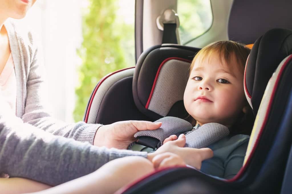 un enfant est dans son siège auto dans la voiture. une personne est en train de lui attacher les sangles.