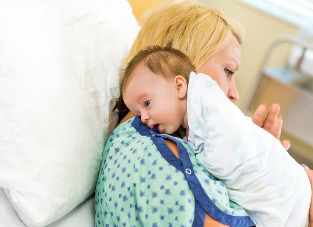 une maman allongée dans un lit tapote le dos de son nouveau-né qui est contre elle. Le bébé est enroulé dans une couverture blanche et posé sur son épaule afin de faire un rot.