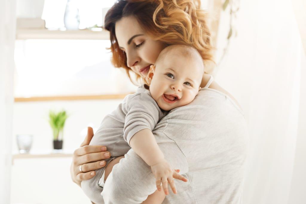 une maman porte son bébé dans ses bras. le bébé semple heureux avec sa tête posée sur l'épaule de sa maman.