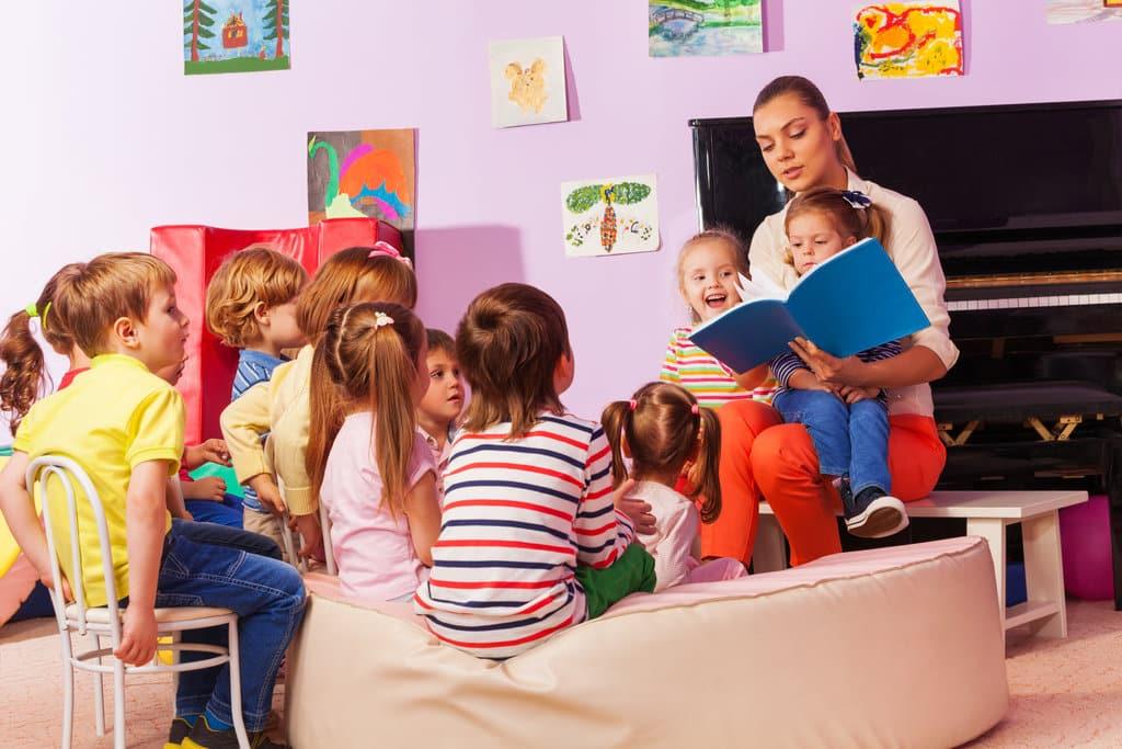 une puéricultrice lit un livre à des enfants installés sur un sofa et chaises