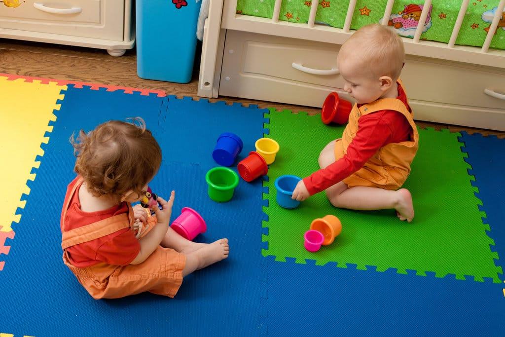 2 jeunes enfant jouent sur un tapis de jeu dans une chambre d'enfant très colorée