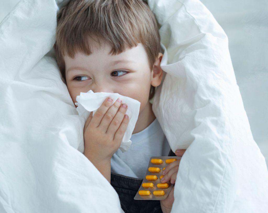 un enfant enveloppé dans une couette blanche porte à son nez un mouchoir et tient dans l'autre main une plaquette de médicaments