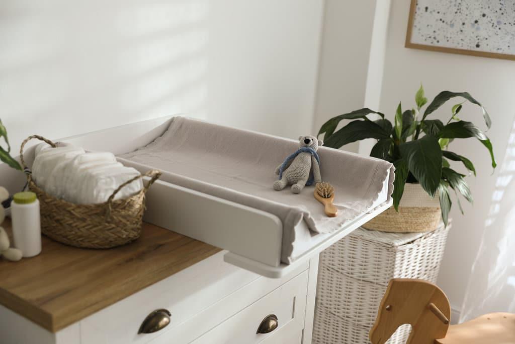 une table à langer est posée sur une commode sur laquelle il y a également des couches neuves dans un panier, du talc, un doudou, une brosse à cheveux, ...
