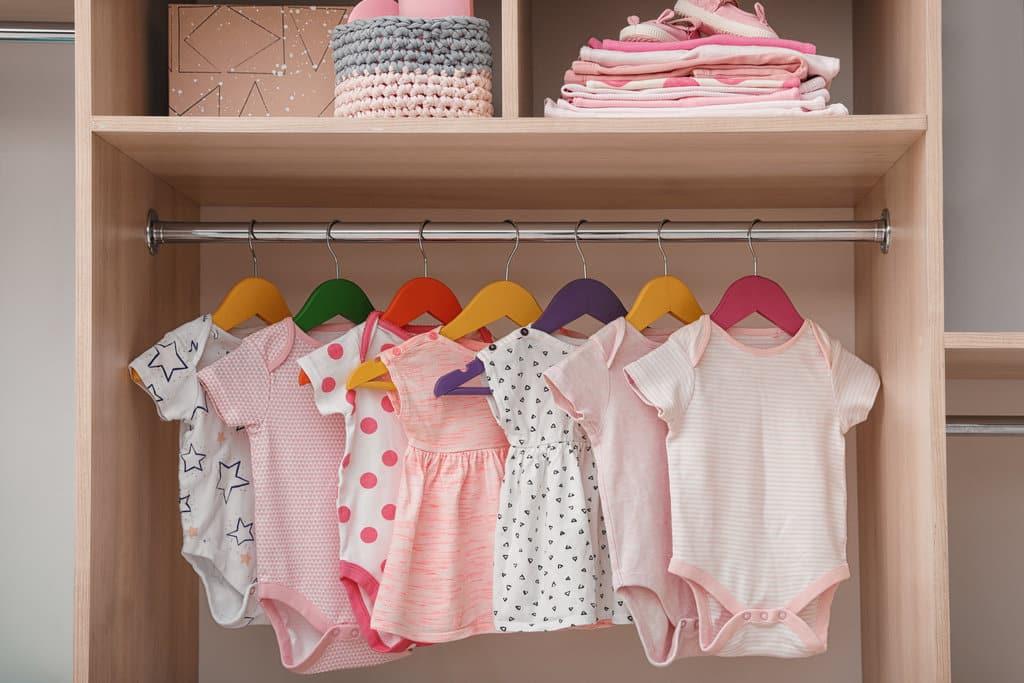 Garde-robe qui contient de jolies vêtements roses et blanc accrochés à des ceintres